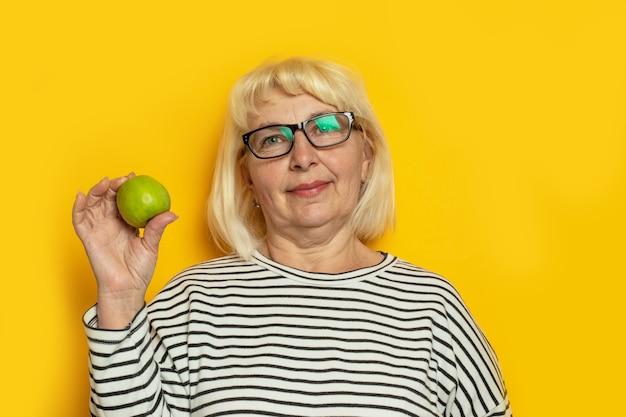 Mulher loira idosa alegre de óculos e roupas casuais segurando uma maçã verde sobre fundo amarelo