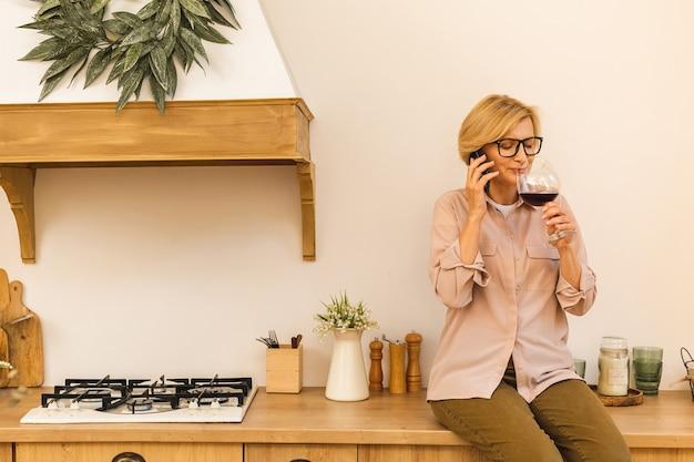Mulher loira idosa sênior madura feliz na cozinha, bebendo vinho tinto. segurando uma taça com vinho. usando o celular.