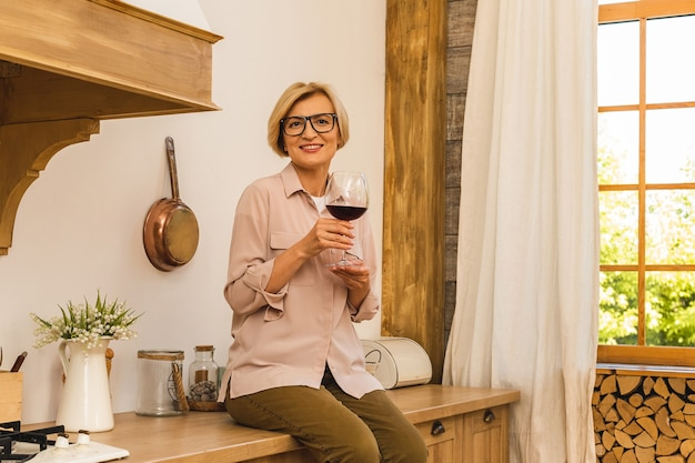 Mulher loira idosa sênior madura feliz na cozinha, bebendo vinho tinto. segurando uma taça com vinho.