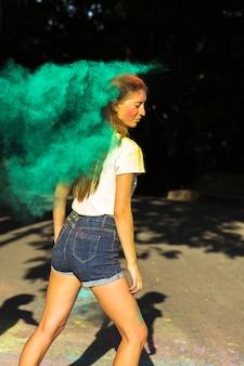 Mulher loira incrível brincando com tinta verde seca holi no parque