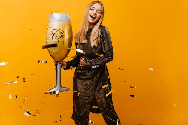 Mulher loira incrível engraçada posando com um grande copo de vinho. mulher branca bem vestida com cabelo loiro dançando no amarelo