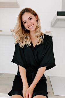 Mulher loira incrível feliz vestindo um roupão de banho preto, sentada na cozinha pela manhã
