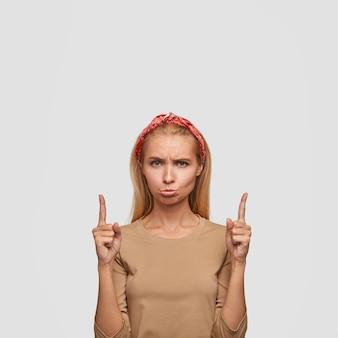 Mulher loira insatisfeita com olhar ofensivo, expressão sombria, aponta com os dois dedos indicadores para cima