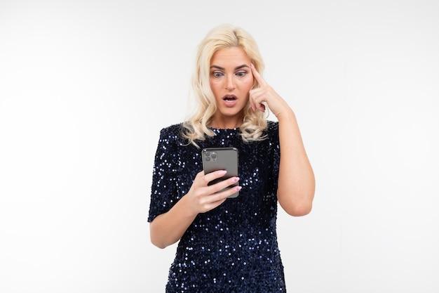 Mulher loira insatisfeita em um vestido azul brilhante, olhando para a tela do telefone em um fundo branco com espaço de cópia