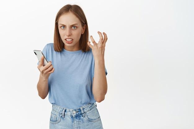 Mulher loira irritada segurando seu telefone celular, cerrar os punhos de raiva, olhando furiosa e irritada, incomodada por alguém online, odeio redes sociais, encostada em uma parede branca com smartphone.