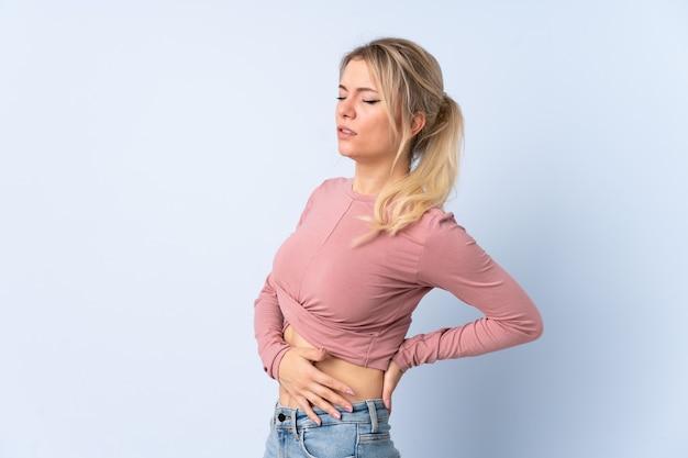 Mulher loira isolada com um azul sofrendo de dor nas costas por ter feito esforço