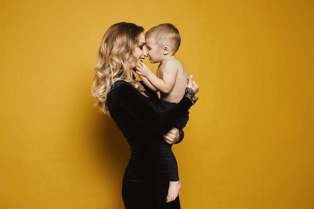 Mulher loira jovem bonita e feliz em um vestido preto elegante com um lindo garotinho em seu colo.