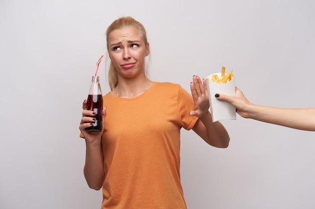 Mulher loira jovem descontente com penteado casual olhando para o lado com beicinho e franzindo a testa com a palma da mão levantada, bebendo refrigerante e se recusando a comer batata frita