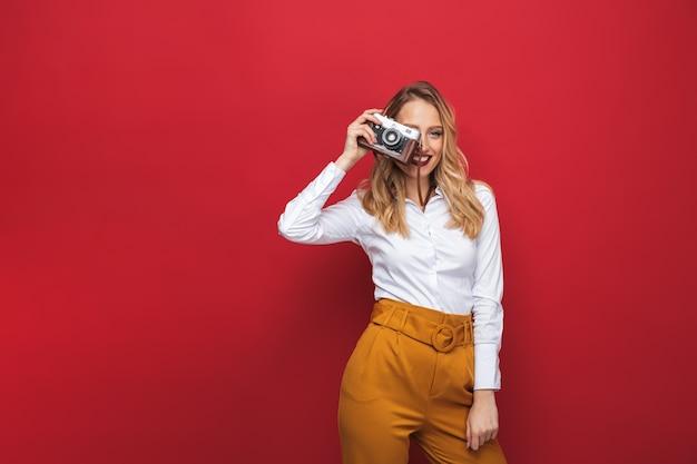 Mulher loira jovem e bonita, feliz, isolada sobre fundo vermelho, segurando uma câmera fotográfica
