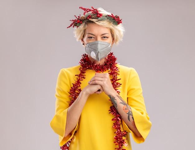 Mulher loira jovem e complicada usando coroa de flores de natal e guirlanda de ouropel em volta do pescoço com máscara protetora, olhando para a câmera, mantendo as mãos juntas isoladas no fundo branco com espaço de cópia