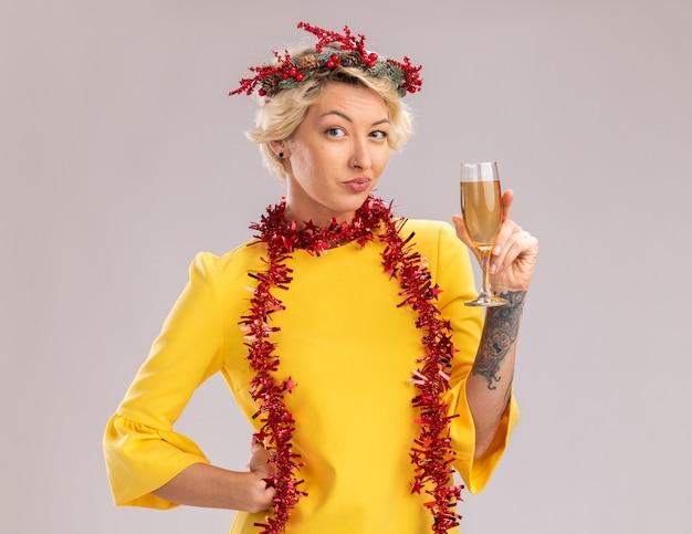 Mulher loira jovem e complicada usando coroa de flores de natal e guirlanda de ouropel em volta do pescoço segurando uma taça de champanhe e mantendo a mão na cintura, olhando para a câmera, isolada no fundo branco