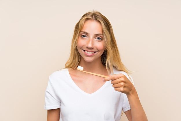 Mulher loira jovem feliz escovar os dentes