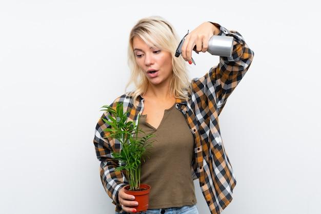 Mulher loira jovem jardineiro segurando uma planta molhando branco