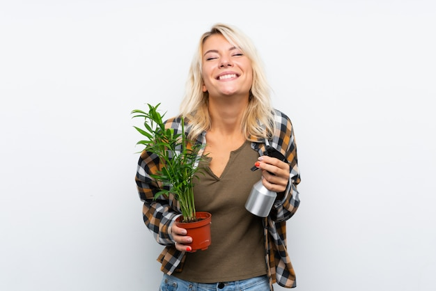 Mulher loira jovem jardineiro segurando uma planta regá-lo sobre fundo branco isolado