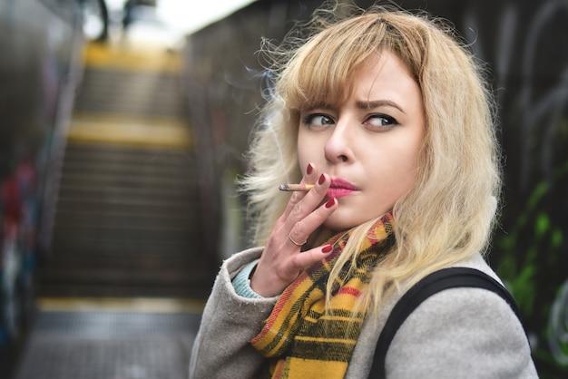 Mulher loira jovem séria fumando um cigarro e olhando de lado na passagem subterrânea.