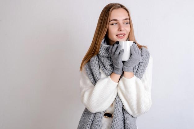 Mulher loira jovem sorridente bonita camisola branca, cachecol e luvas segurando um copo branco de bebida nas mãos dela.