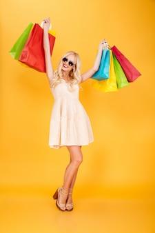 Mulher loira jovem sorridente segurando sacolas de compras.