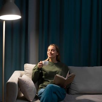 Mulher loira, lendo um livro no sofá