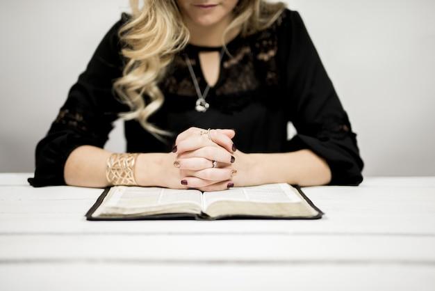 Mulher loira lendo uma bíblia sobre a mesa