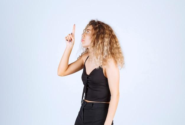 Mulher loira levantando a mão e apontando algo acima com emoções.
