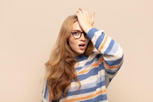 Mulher loira levantando a palma da mão na testa pensando oops, depois de cometer um erro estúpido ou lembrar, sentindo-se burra
