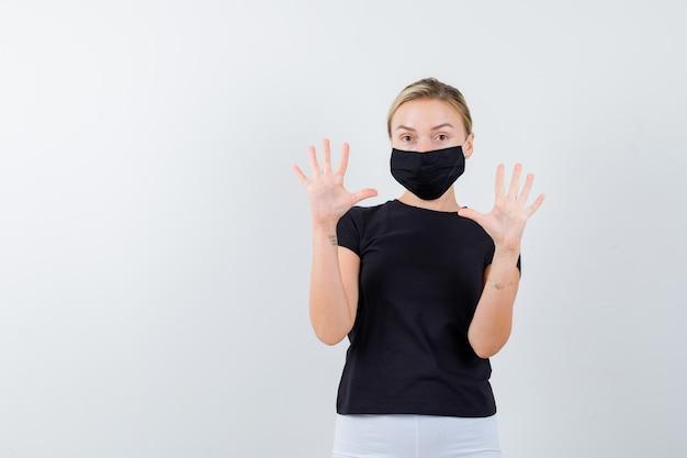 Mulher loira levantando as palmas das mãos em gesto de rendição em camiseta preta, calça branca