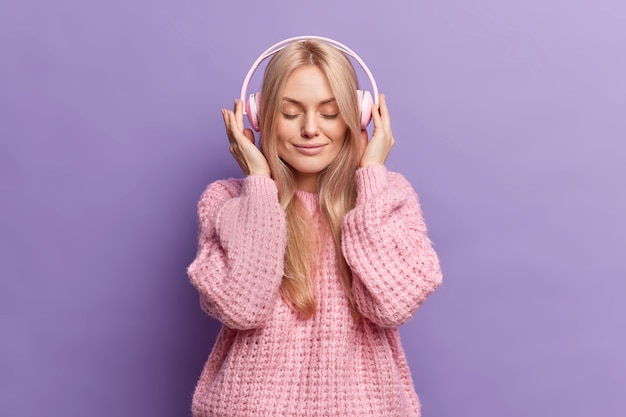 Mulher loira linda e calma mantém as mãos nos fones de ouvido estéreo, os olhos fechados ouve música aprecia cada música vestida com um macacão