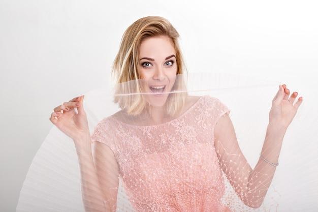 Mulher loira linda e sensual em um vestido rosa claro, dançando e se divertindo em um fundo cinza