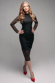 Mulher loira linda elegante vestido preto sorrindo.