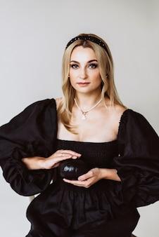 Mulher loira linda em um vestido de linho preto com uma abóbora nas mãos. moda étnica, tecido natural. festa de halloween. foco seletivo suave.