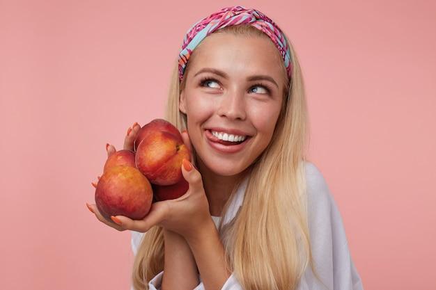 Mulher loira linda engraçada posando com pêssegos nas mãos, olhando jocosamente para o lado e puxando a língua para fora