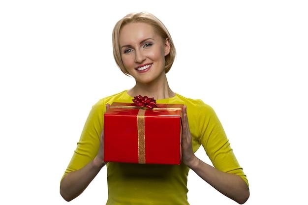 Mulher loira linda feliz com caixa de presente vermelha grande, isolada na parede branca. recebendo presentes de. jovem mulher atraente tendo um presente.