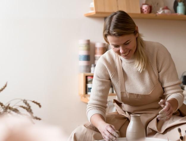 Mulher loira linda feliz fazendo vaso na roda de oleiro na oficina de cerâmica