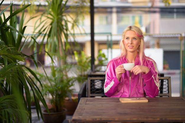 Mulher loira linda jovem feliz bebendo café na cafeteria