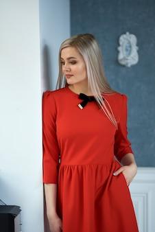 Mulher loira linda sensual posando em vestido vermelho. garota com cabelo comprido.