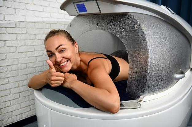 Mulher loira linda sorridente mostrando o polegar para a câmera enquanto desfruta de um tratamento de cuidado corporal profissional na cápsula de spa.