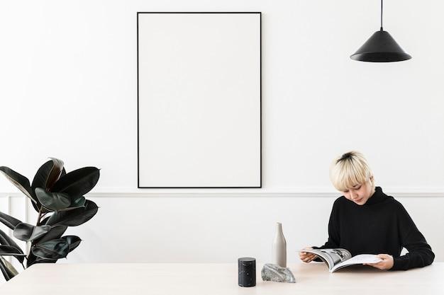 Mulher loira loira lendo uma revista com uma moldura em branco na parede