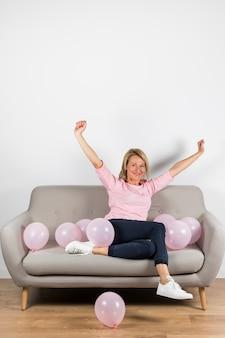 Mulher loira madura animada sentado no sofá com balões rosa, levantando os braços