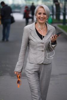 Mulher loira madura caminha em um parque público, ouve música com fones de ouvido e sorrisos, foco seletivo