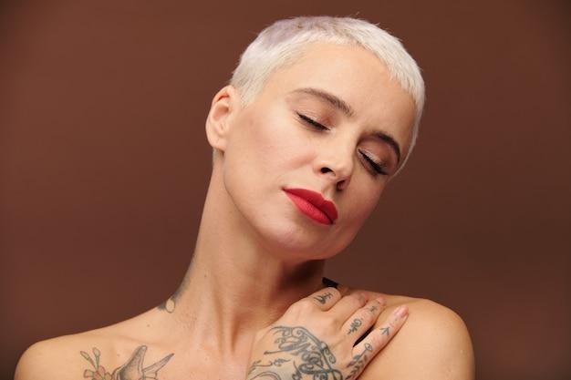 Mulher loira madura com aparência de homem com tatuagens nas mãos, dedos, ombro e pescoço, mantendo os olhos fechados enquanto fica em pé na frente da câmera em isolamento
