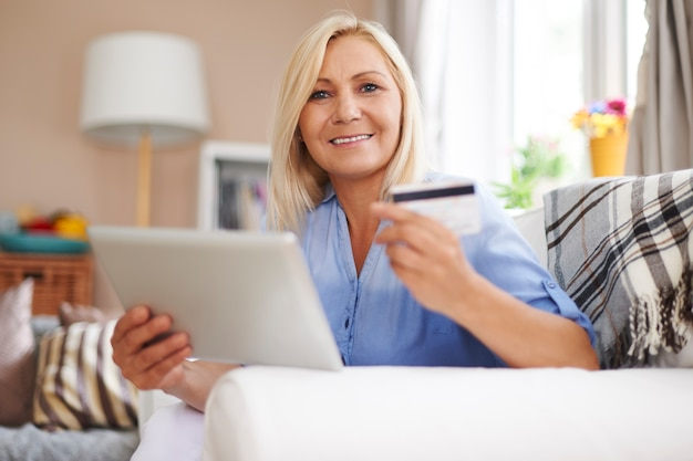 Mulher loira madura com tablet digital e cartão de crédito