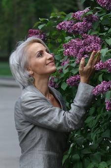 Mulher loira madura de terno cinza caminha no jardim, admira flores e sorri, com foco seletivo