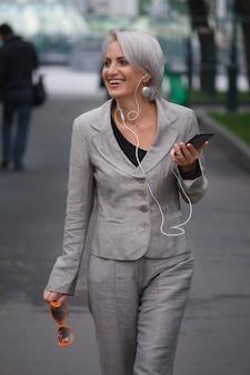 Mulher loira madura de terno cinza caminhando em um parque público, ouvindo música com fones de ouvido e sorrindo