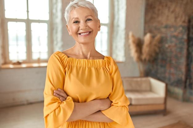 Mulher loira madura e confiante atraente usando um vestido amarelo, cruzando os braços no peito e sorrindo alegremente para a câmera, posando em seu apartamento recém-reformado com sofá e janelas ao fundo