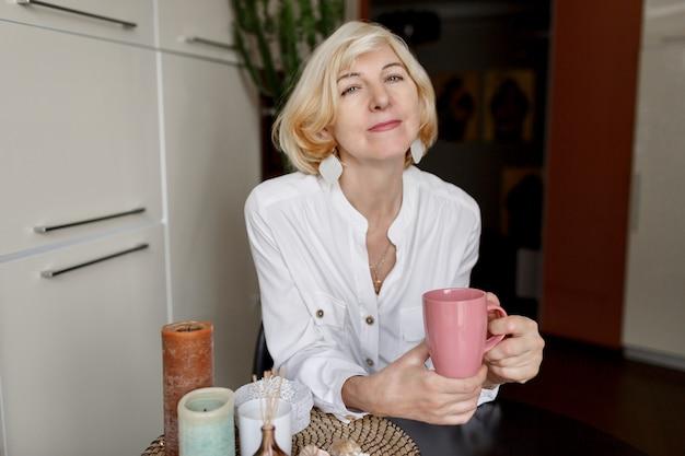 Mulher loira madura muito magro, aproveitando a manhã com café