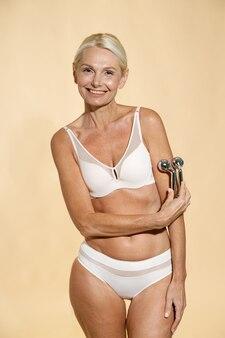 Mulher loira madura natural em roupa íntima com corpo em forma e pele brilhante segurando um elevador de metal anti