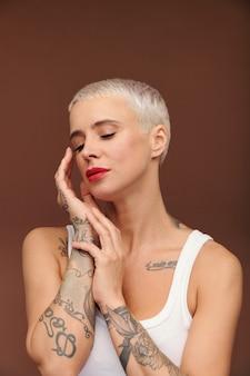 Mulher loira madura, parecida com um homem, com tatuagens nos braços, tocando seu rosto com as mãos e mantendo os olhos fechados em frente à câmera