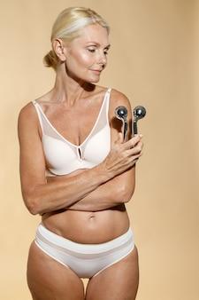 Mulher loira madura perfeita em roupa íntima com pele brilhante segurando o rolo facial de metal sorrindo de lado
