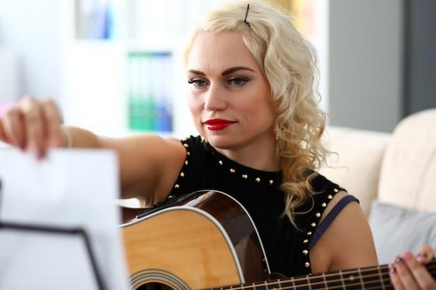 Mulher loira madura, virando as páginas de notas enquanto toca violão ocidental