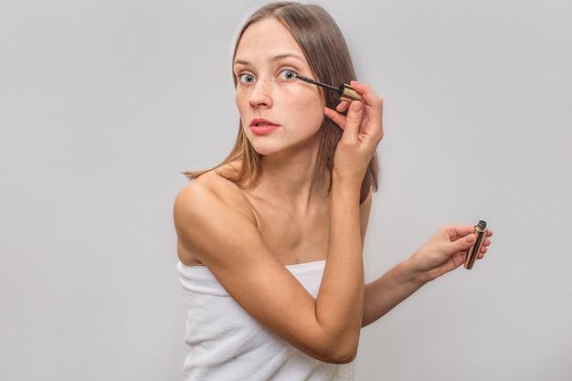 Mulher loira magro fica e olha. ela usa rímel para cílios. ela está concentrada e calma.